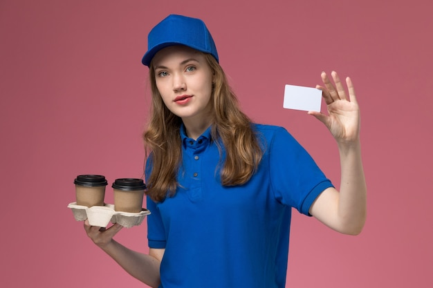 Front view female courier in blue uniform holding brown delivery coffee cups and card on the pink background service uniform delivering company job
