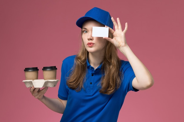 Front view female courier in blue uniform holding brown delivery coffee cups and card on the pink desk service uniform delivering company job