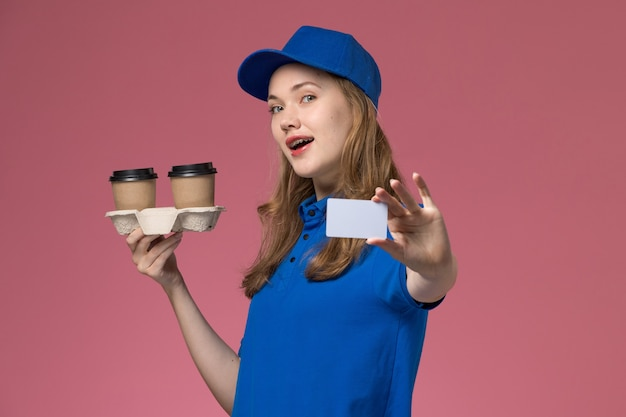 Front view female courier in blue uniform holding brown delivery coffee cups and card on pink desk service uniform delivering company