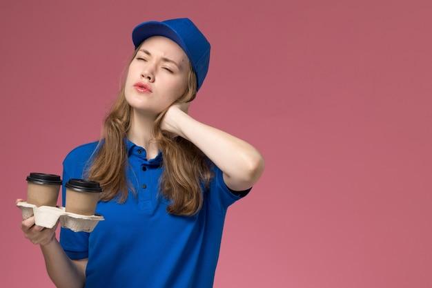 Corriere femminile di vista frontale in uniforme blu che tiene le tazze di caffè di consegna marroni che hanno mal di collo su uniforme di servizio rosa del fondo che consegna il lavoro dell'azienda