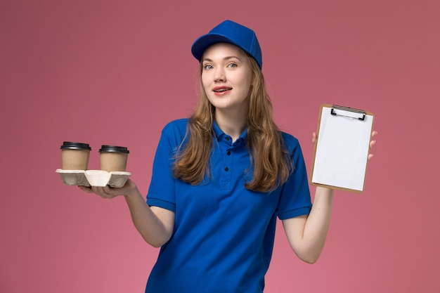Front view female courier in blue uniform holding brown delivery coffee cups and notepad on the pink desk service uniform company job