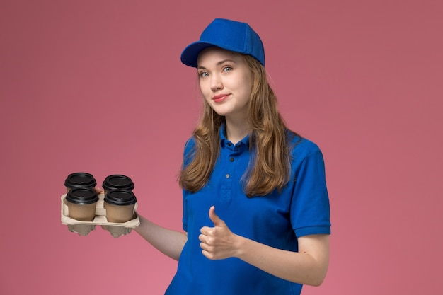 Front view female courier in blue uniform holding brown delivery coffee cups showing like sign on pink desk service uniform company worker
