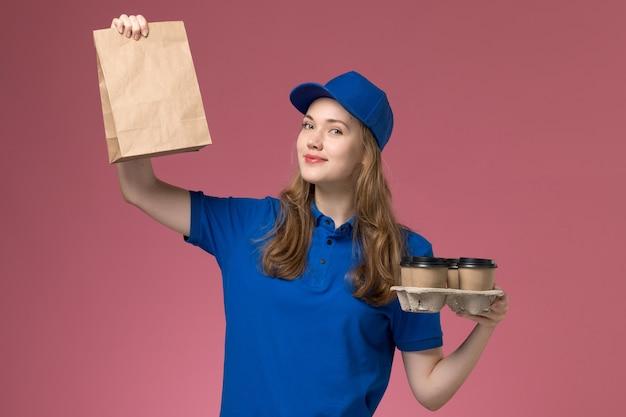 Corriere femminile di vista frontale in uniforme blu che tiene le tazze di caffè marroni di consegna con il pacchetto dell'alimento che sorride sull'operaio dell'azienda dell'uniforme di servizio dello scrittorio rosa