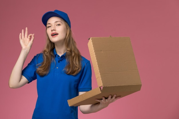 Front view female courier in blue uniform holding an empty food delivery box on the pink desk worker service uniform company job
