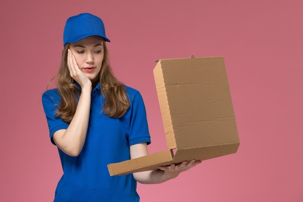 Front view female courier in blue uniform holding empty food delivery box on pink desk worker service uniform company job