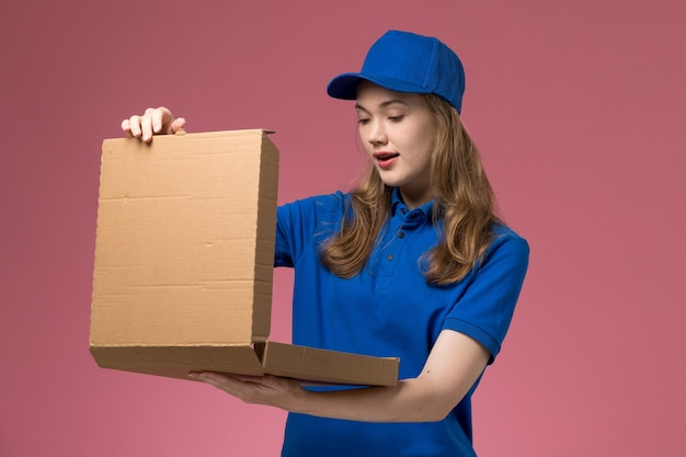 Front view female courier in blue uniform holding food box opening it on the pink background job worker service uniform company