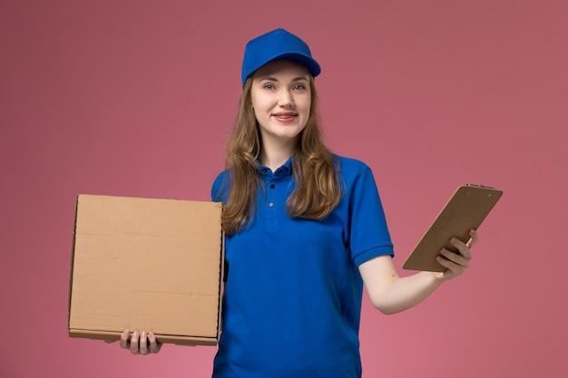 Corriere femminile di vista frontale in uniforme blu che tiene la scatola di consegna del cibo e il blocco note sul lavoratore della società di lavoro uniforme di servizio scrivania rosa chiaro