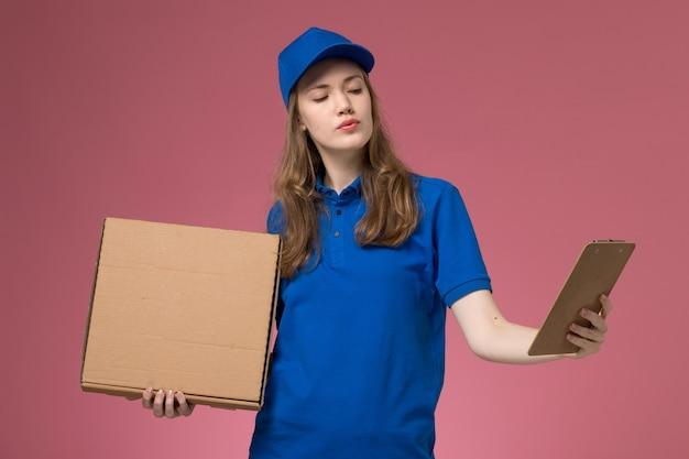 Corriere femminile di vista frontale in uniforme blu che tiene la scatola di consegna del cibo e il blocchetto per appunti sul lavoratore della compagnia di lavoro uniforme di servizio scrivania rosa
