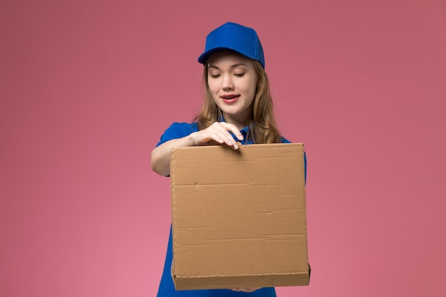 Front view female courier in blue uniform holding food delivery box opening it on pink desk job service uniform company