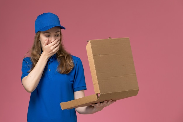 Front view female courier in blue uniform holding food delivery box opening it with shocked expression on pink desk worker service uniform company job