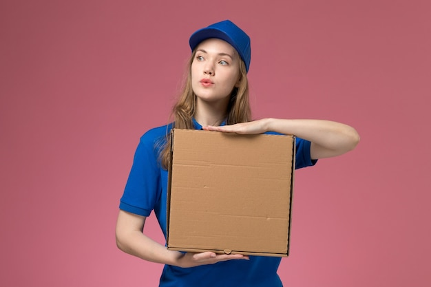 Front view female courier in blue uniform holding food delivery box on pink background service uniform company