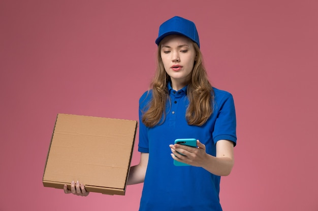Front view female courier in blue uniform holding food delivery box and using phone on pink desk service uniform company job