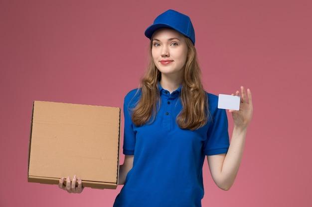 Corriere femminile di vista frontale in uniforme blu che tiene scatola di consegna del cibo e carta bianca sul lavoro dell'azienda uniforme di servizio scrivania rosa