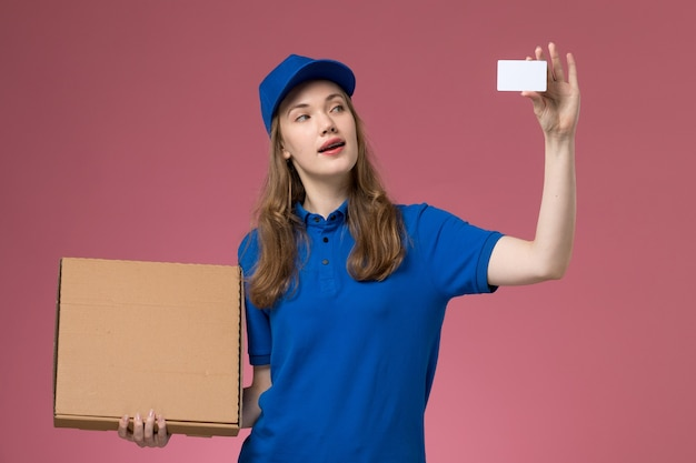Front view female courier in blue uniform holding food delivery box and white card on the pink desk service uniform company job