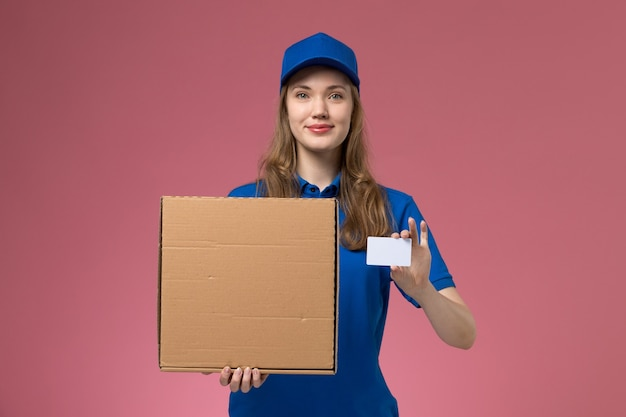 Front view female courier in blue uniform holding food delivery box and white card on the pink desk service uniform company worker