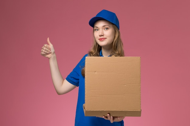 Front view female courier in blue uniform holding food delivery box with smile on pink background job service uniform company