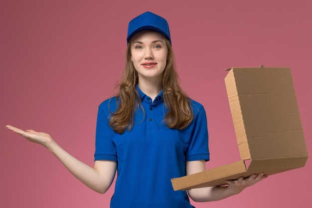 Front view female courier in blue uniform holding food delivery box with smile on the pink desk worker service uniform company job