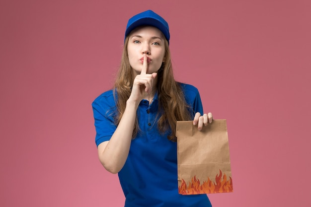 Front view female courier in blue uniform holding food package showing silence sign on pink desk job worker service uniform company