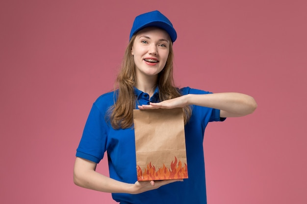 Corriere femminile di vista frontale in uniforme blu che tiene il pacchetto dell'alimento che sorride sull'azienda dell'uniforme di servizio dell'operaio del fondo rosa