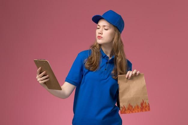 Corriere femminile di vista frontale in uniforme blu che tiene blocco note e pacchetto di cibo sulla società uniforme di servizio di lavoro scrivania rosa chiaro