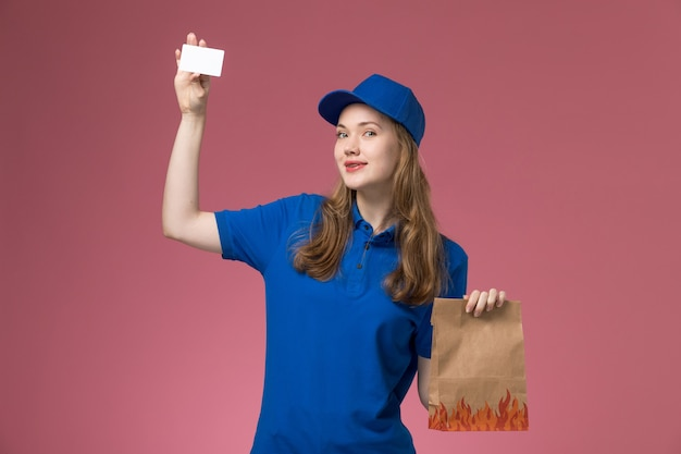 Corriere femminile di vista frontale in uniforme blu sorridente che tiene carta bianca e pacchetto di cibo sul lavoro aziendale uniforme di servizio scrivania rosa
