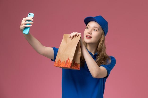 Corriere femminile di vista frontale in uniforme blu che prende un selfie con il pacchetto dell'alimento sul lavoro dell'azienda dell'uniforme di servizio di luce rosa scrivania