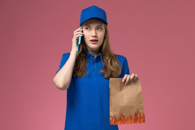 Corriere femminile di vista frontale in uniforme blu parlando al telefono mentre si tiene il pacchetto di cibo sul lavoro aziendale uniforme di servizio scrivania luce rosa