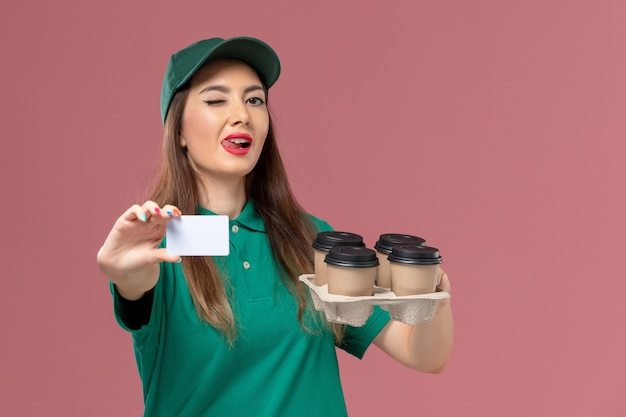 Front view female courier in green uniform and cape holding card and delivery coffee cups on light pink wall service uniform delivery job
