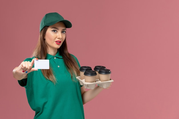 Front view female courier in green uniform and cape holding card and delivery coffee cups on pink desk service uniform delivery