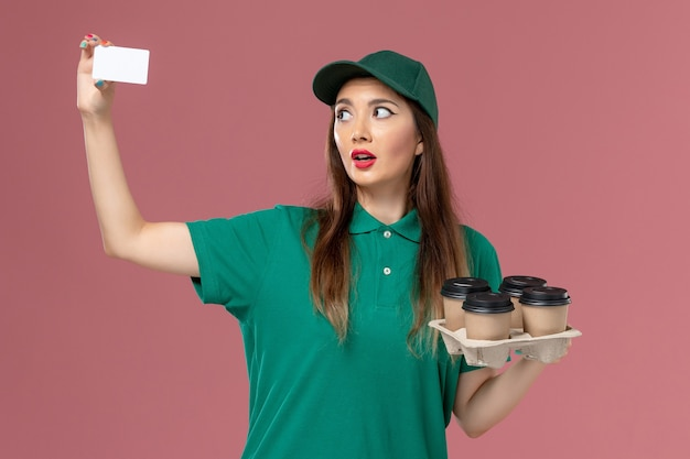 Front view female courier in green uniform and cape holding card and delivery coffee cups on pink wall service uniform delivery job work worker