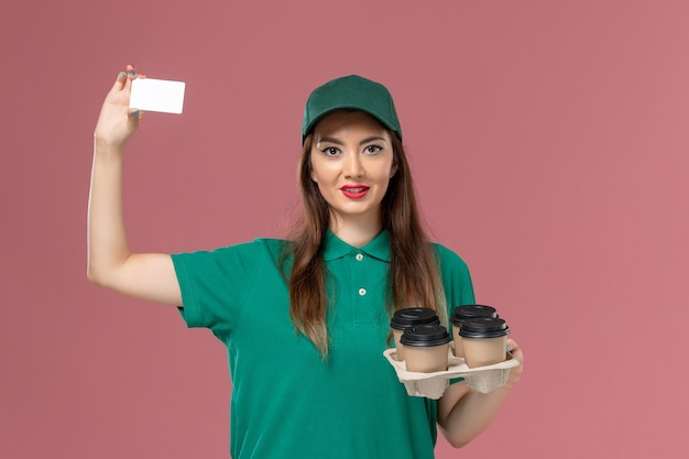 Front view female courier in green uniform and cape holding card and delivery coffee cups on pink wall service uniform delivery job work