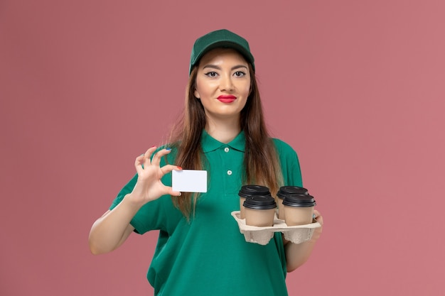 Front view female courier in green uniform and cape holding card and delivery coffee cups on pink wall service uniform delivery job worker