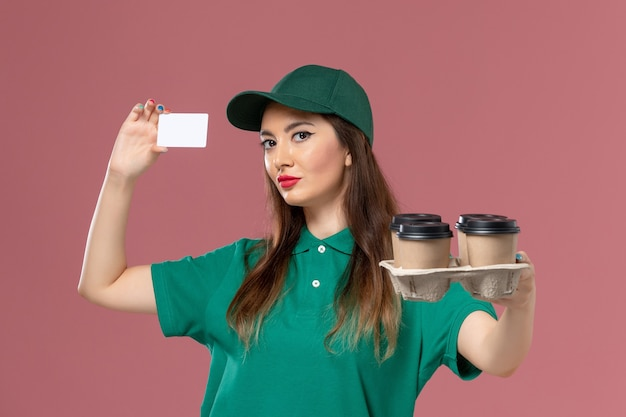 Front view female courier in green uniform and cape holding card and delivery coffee cups on the pink wall service uniform delivery job worker