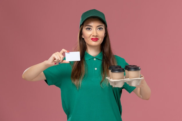 Front view female courier in green uniform and cape holding card and delivery coffee cups on pink wall service uniform delivery job