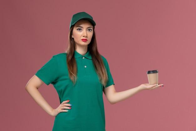 Corriere femminile di vista frontale in uniforme verde e tazza di caffè di consegna della tenuta del capo sulla consegna uniforme di lavoro di servizio della parete rosa chiaro