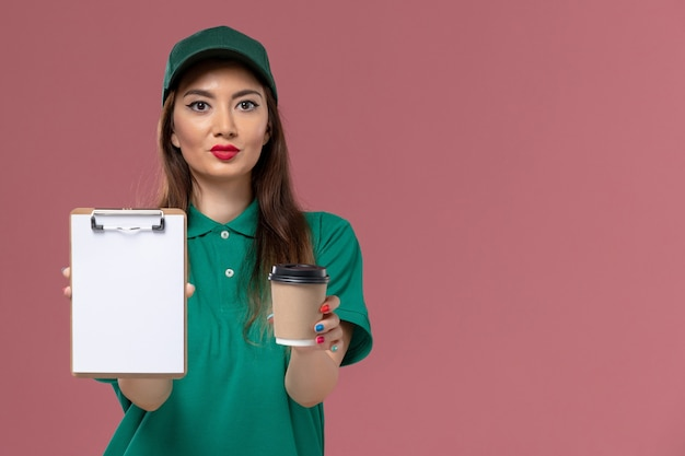 Front view female courier in green uniform and cape holding delivery coffee cup and notepad on pink wall service job uniform delivery female company