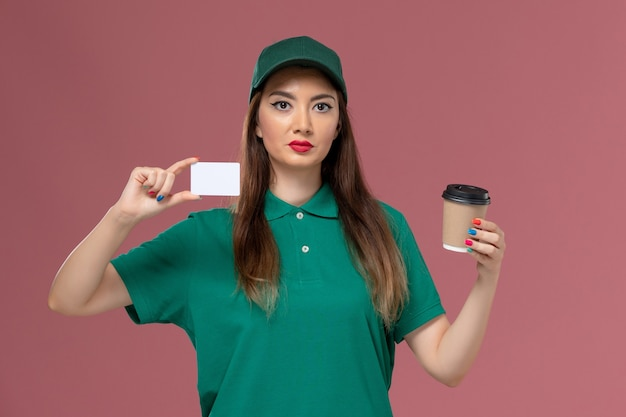 Front view female courier in green uniform and cape holding delivery coffee cup with card on pink wall service job uniform delivery work
