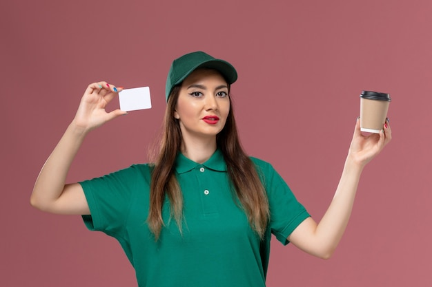 Front view female courier in green uniform and cape holding delivery coffee cup with card on pink wall service job uniform delivery