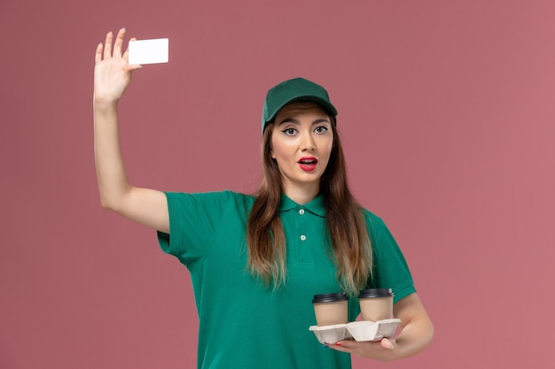 Front view female courier in green uniform and cape holding delivery coffee cups and card on pink wall service job uniform delivery lady