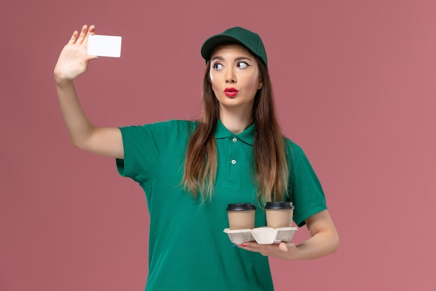 Front view female courier in green uniform and cape holding delivery coffee cups and card on pink wall service job uniform delivery worker