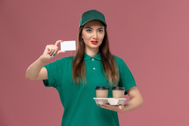 Front view female courier in green uniform and cape holding delivery coffee cups and card on pink wall service job uniform delivery