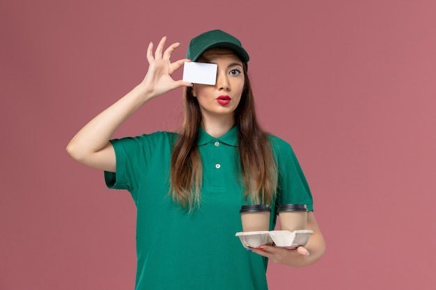 Front view female courier in green uniform and cape holding delivery coffee cups and card on the pink wall service job uniform delivery