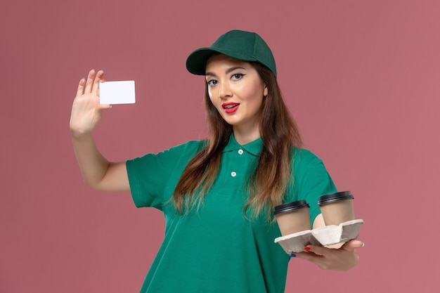 Front view female courier in green uniform and cape holding delivery coffee cups and card on pink wall service job uniform worker delivery