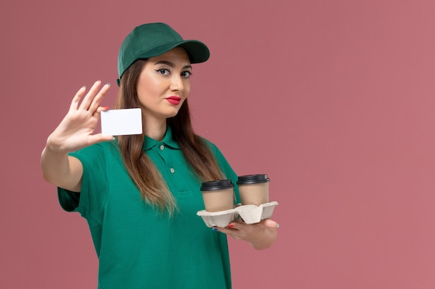 Front view female courier in green uniform and cape holding delivery coffee cups and card on pink wall service job work uniform delivery