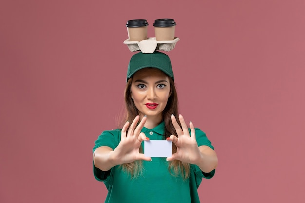 Front view female courier in green uniform and cape holding delivery coffee cups and card on pink wall worker service job uniform delivery