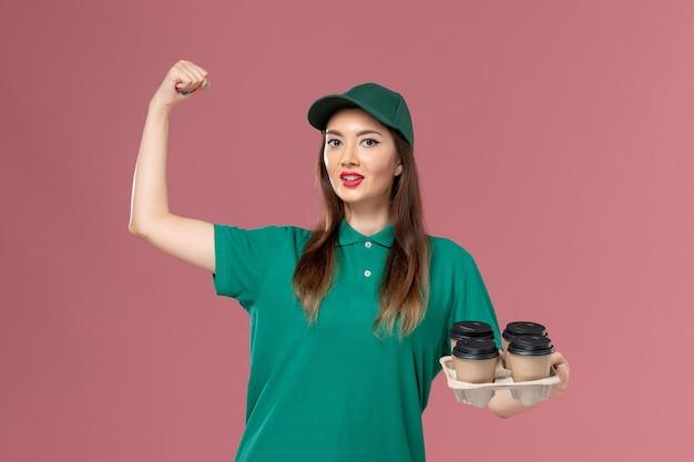 Corriere femminile di vista frontale in uniforme verde e mantello che tiene le tazze di caffè di consegna che flettono sul lavoro di consegna uniforme di servizio della parete rosa chiaro