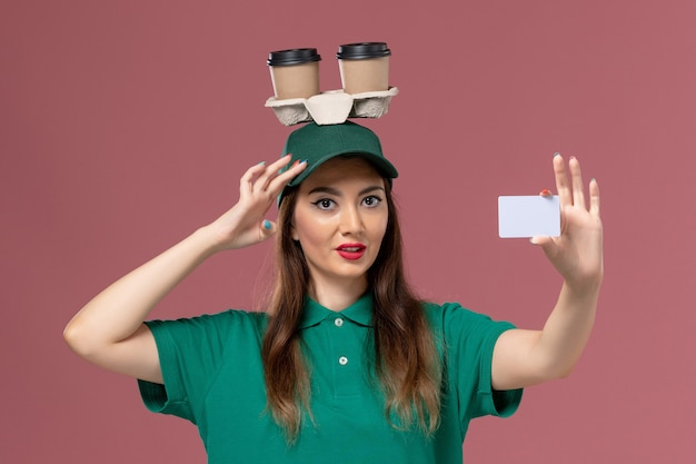 Front view female courier in green uniform and cape holding delivery coffee cups on her head and card on pink wall service job uniform delivery