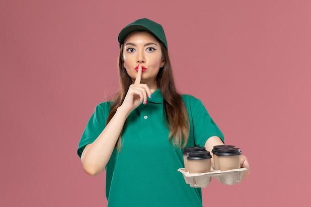 Corriere femminile di vista frontale in uniforme verde e mantello che tiene le tazze di caffè di consegna sul lavoro di consegna uniforme di servizio della parete rosa chiaro