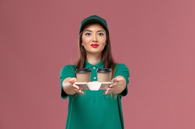Corriere femminile di vista frontale in uniforme verde e mantello che tiene le tazze di caffè di consegna sul lavoro di consegna dell'uniforme di lavoro di servizio dell'azienda della parete rosa