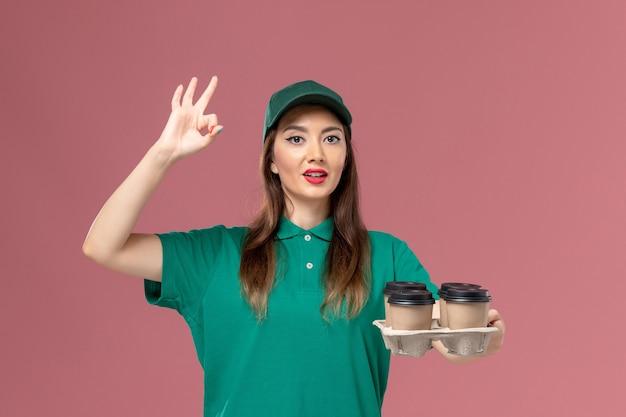 Corriere femminile di vista frontale in uniforme verde e tazze di caffè di consegna della tenuta del capo che posano sul lavoro di consegna dell'uniforme di servizio della parete rosa chiaro